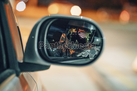reflection of spaceman in wing mirror