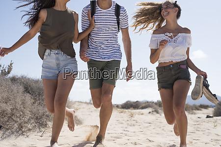 friends having fun running barefoot on
