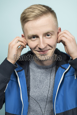 portrait of smiling young man putting