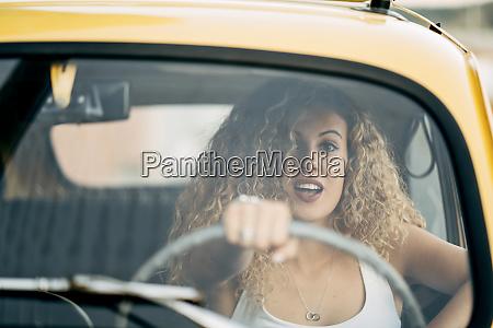 portrait of surprised blond woman driving