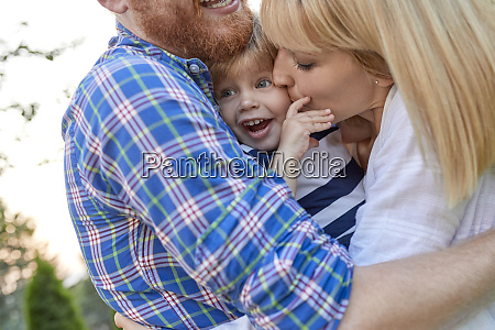 happy parents hugging her daughter outdoors