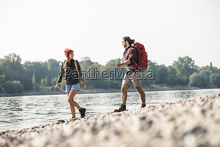 young couple with backpacks walking at