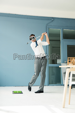 businessman wearing vr glasses playing golf