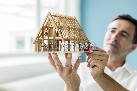geschaeftsmann haelt modellhaus im amt