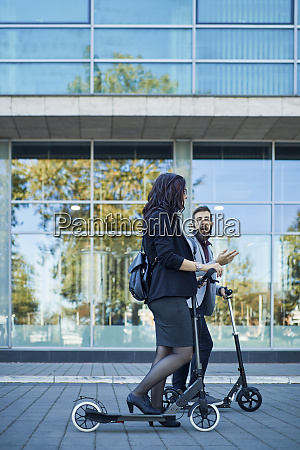 businessman and businesswoman with scooters talking