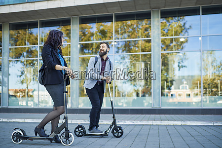 smiling businessman and businesswoman with scooters