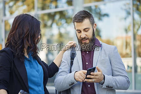 businessman and businesswoman with cell phone