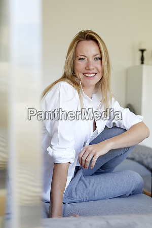 happy woman sitting on couch laughing