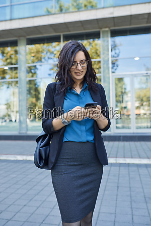 smiling businesswoman using cell phone in