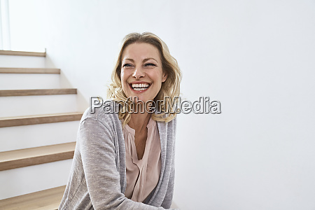 laughing woman sitting on stairs at