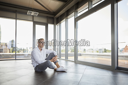 businessman sitting in empty room looking