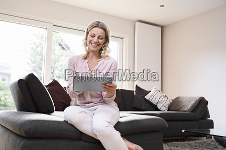 happy woman sitting on couch using
