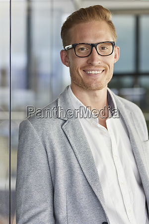 portrait of smiling redheaded businessman wearing