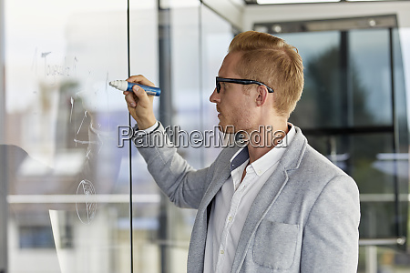 businessman writing on glass pane in