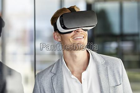 smiling businessman wearing vr glasses