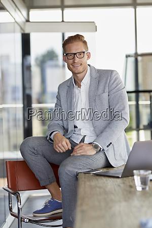 portrait of smiling businessman with laptop
