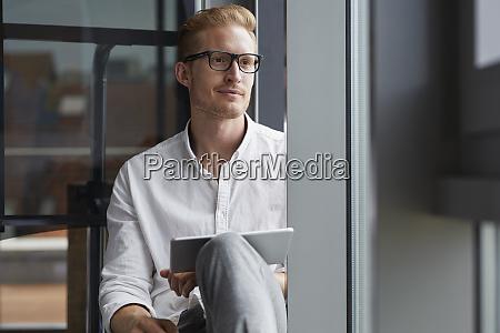 smiling businessman sitting on windowsill with