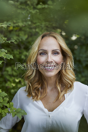 portrait of smiling blond woman outdoors