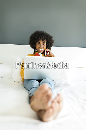 happy woman lying on bed with