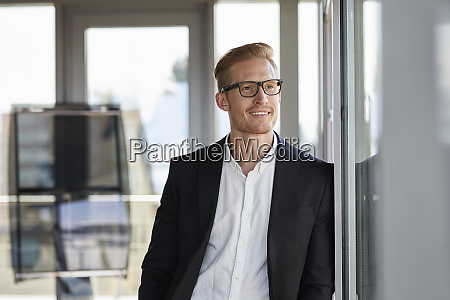 smiling businessman in office looking out
