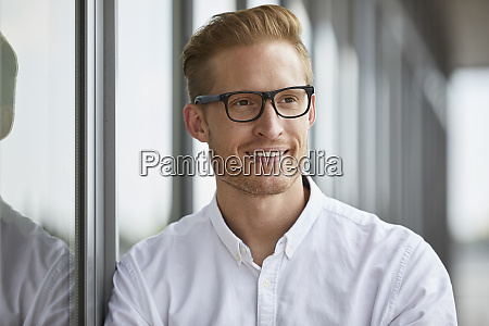 portrait of smiling businessman leaning against
