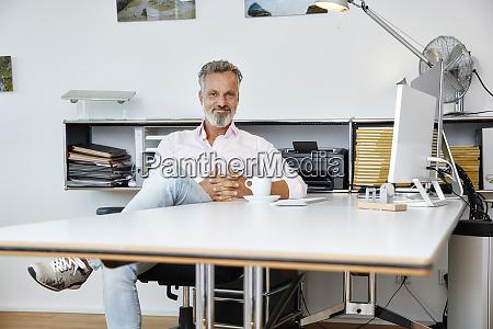 portrait of confident businessman sitting at