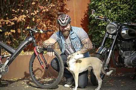 smiling man with dog between motorbike