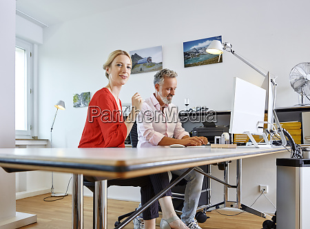 two colleagues working together at desk