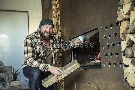 portrait of bearded man lighting fireplace