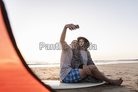 couple camping on the beach taking