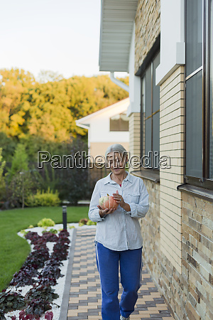 smiling senior woman with harvested pumpkin