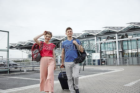 smiling couple walking outside airport