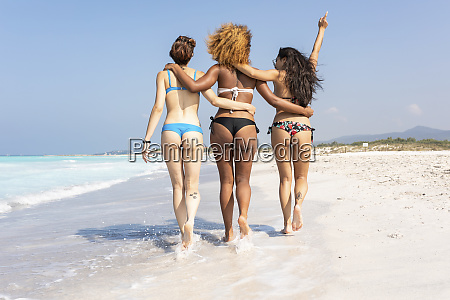 happy girl friends walking on the