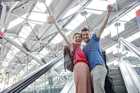 happy couple cheering on escalator at