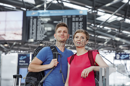 smiling couple at arrival departure board