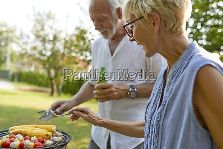 senior couple having a barbecue in