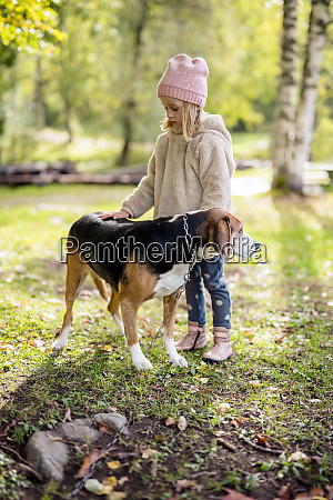 little girl stroking dog in autumnal