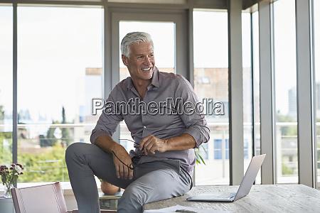smiling mature man with laptop sitting