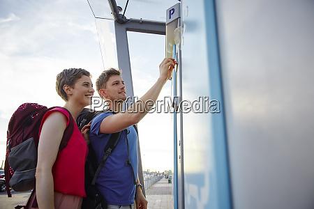 laechelnde ehepaar am flughafen putting muenzparkplatz