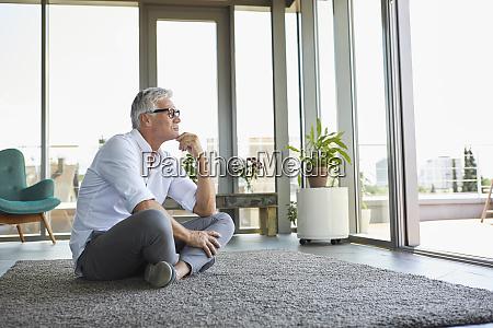 pensive mature man sitting on carpet