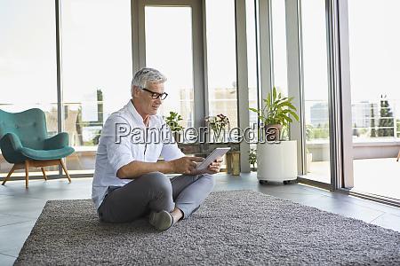 mature man sitting on carpet at