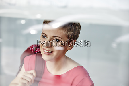 portrait of smiling woman with backpack