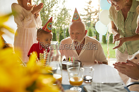 happy extended family blowing out candles