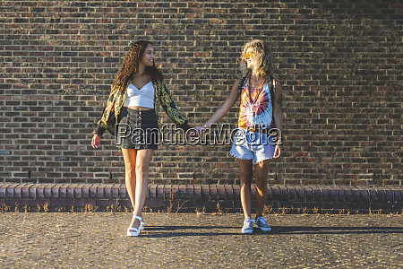two young women holding hands in