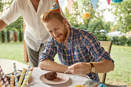 man eating cake on a birthday
