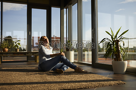 relaxed mature woman sitting on carpet
