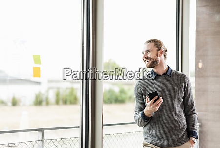 laughing young businessman with cell phone