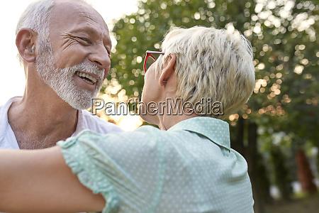 happy senior couple hugging outdoors