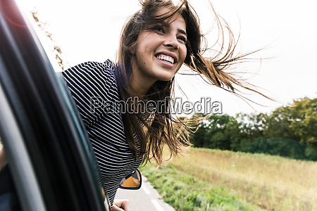 happy young woman leaning out of