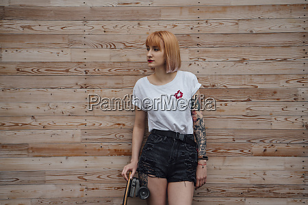 young woman standing at wooden wall